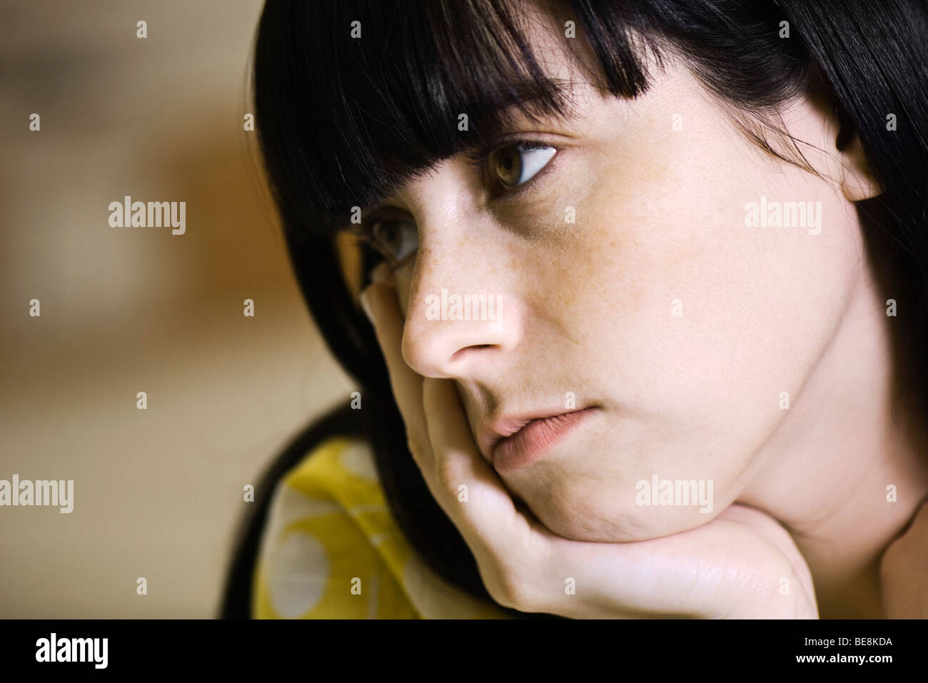 Young woman contemplatively looking away - Stock Image