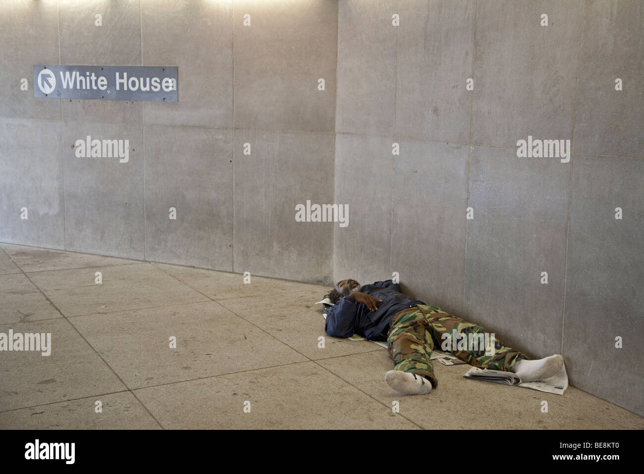 Washington, DC - A homeless man sleeps at the entrance to a Metro subway station near the White House. - Stock Image