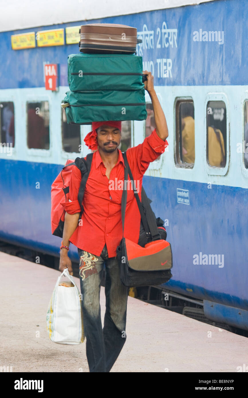 Porter carrying luggage at the railway station in Hyderabad India - Stock Image