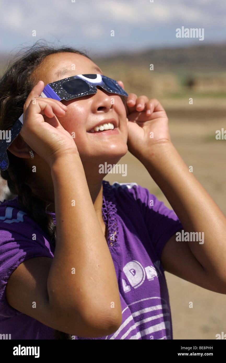 Mongolian girl looking at eclipse through eclipse glasses; Mongools meisje kijkend naar zonsverduistering door eclipsbrilletje - Stock Image
