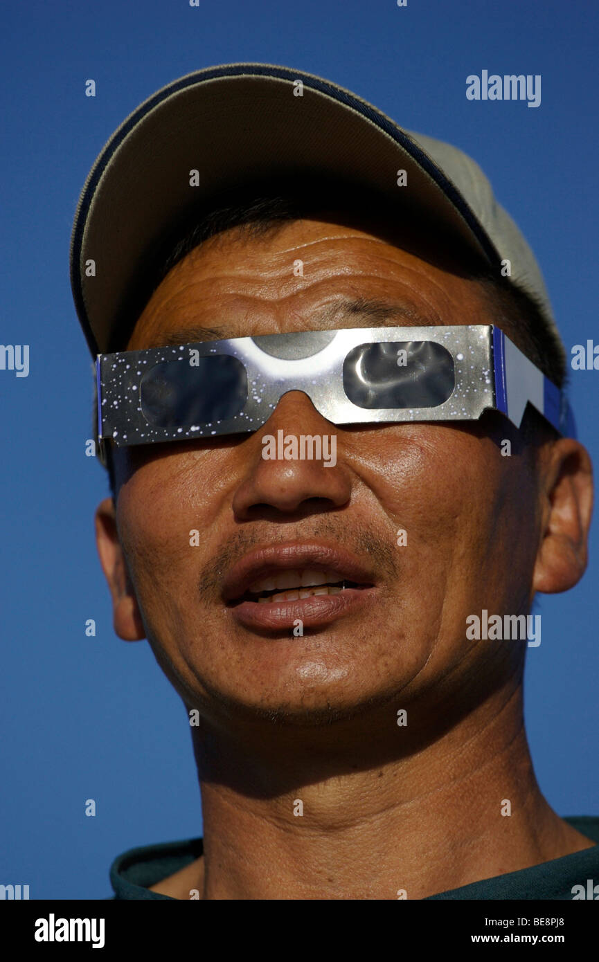 Mongolian man looking at eclipse through eclipse glasses; Mongoolse man kijkend naar zonsverduistering door eclipsbrilletje - Stock Image
