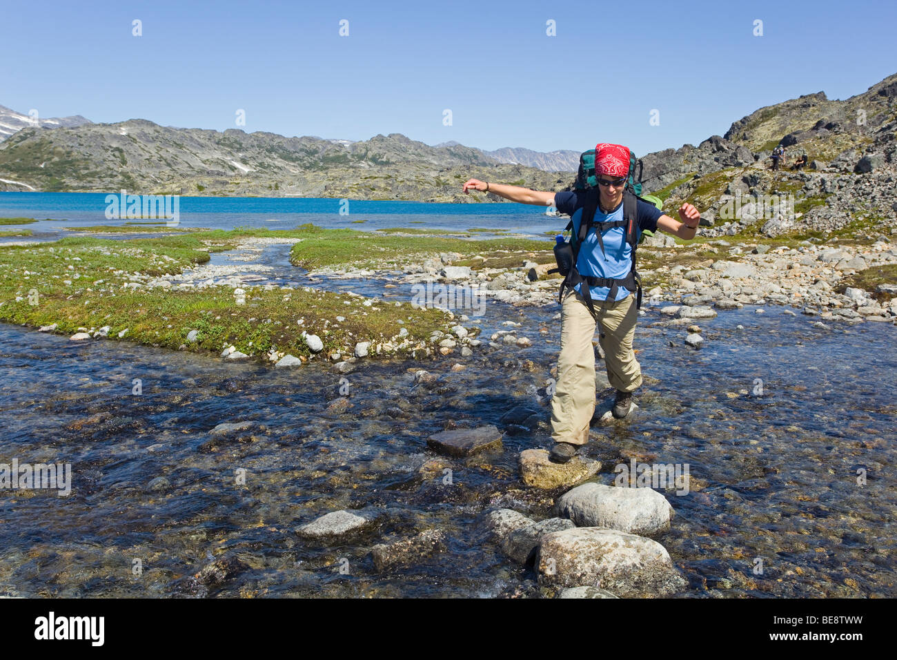 Young woman crossing a creek, hiking, backpacking, hiker with backpack, historic Chilkoot Trail, Chilkoot Pass, Stock Photo