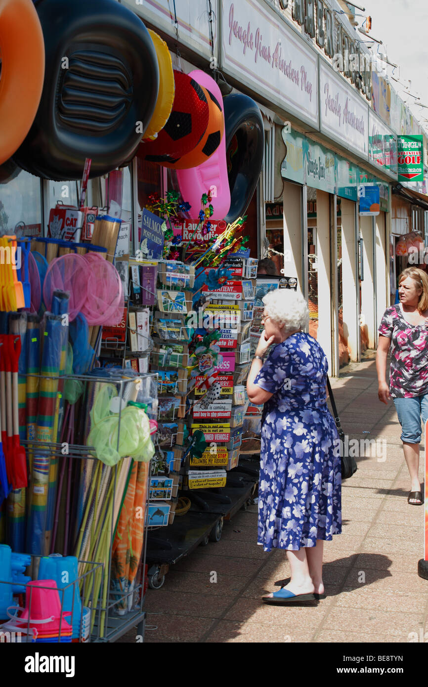 elderly lady looking at postcards at a beach front shop - Stock Image