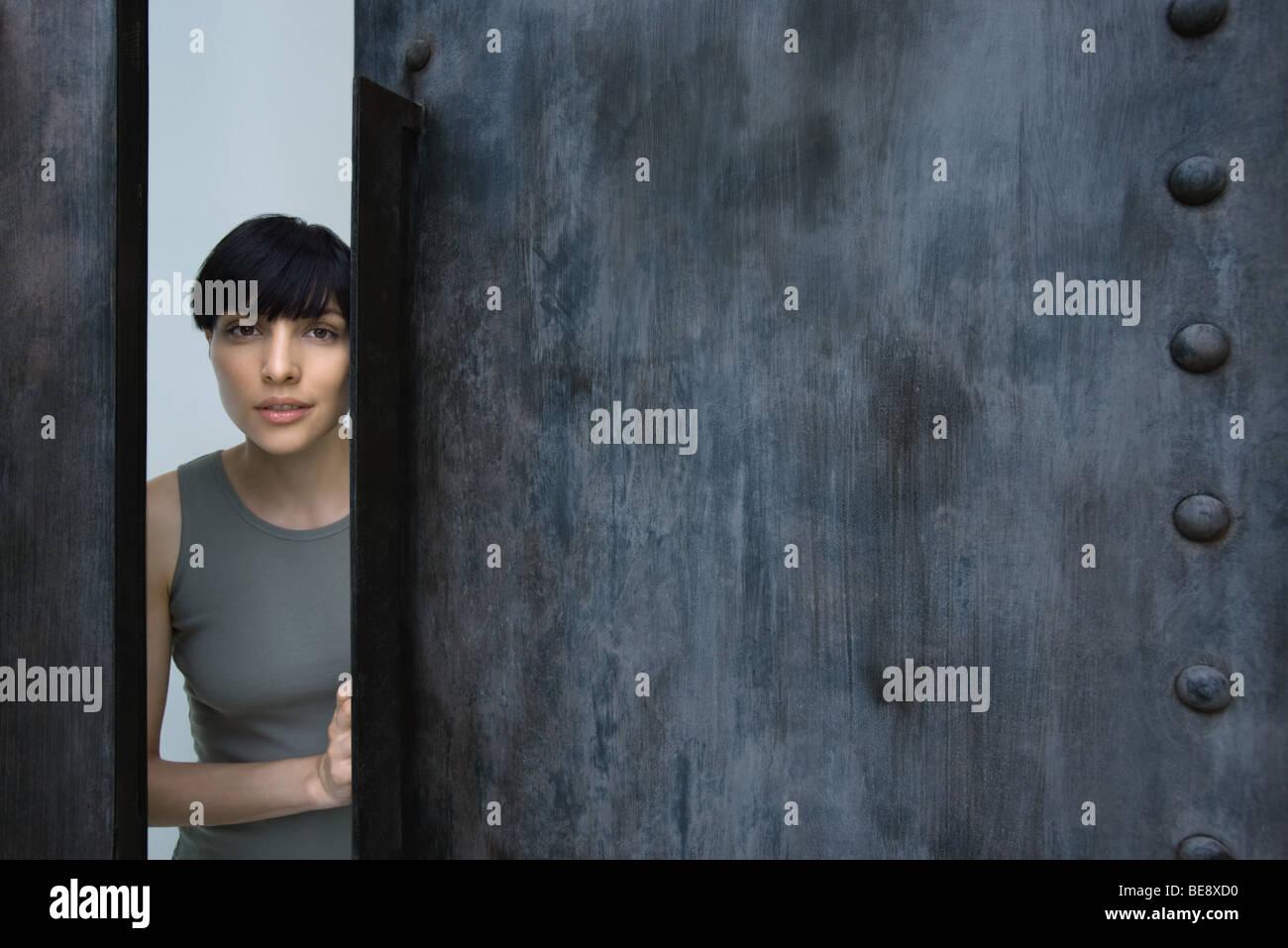 Woman opening door, looking at camera - Stock Image