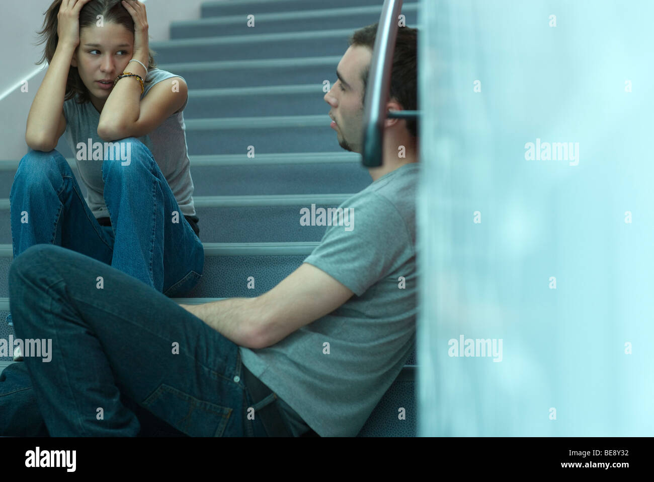 Young couple sitting on stairs, having tense conversation - Stock Image