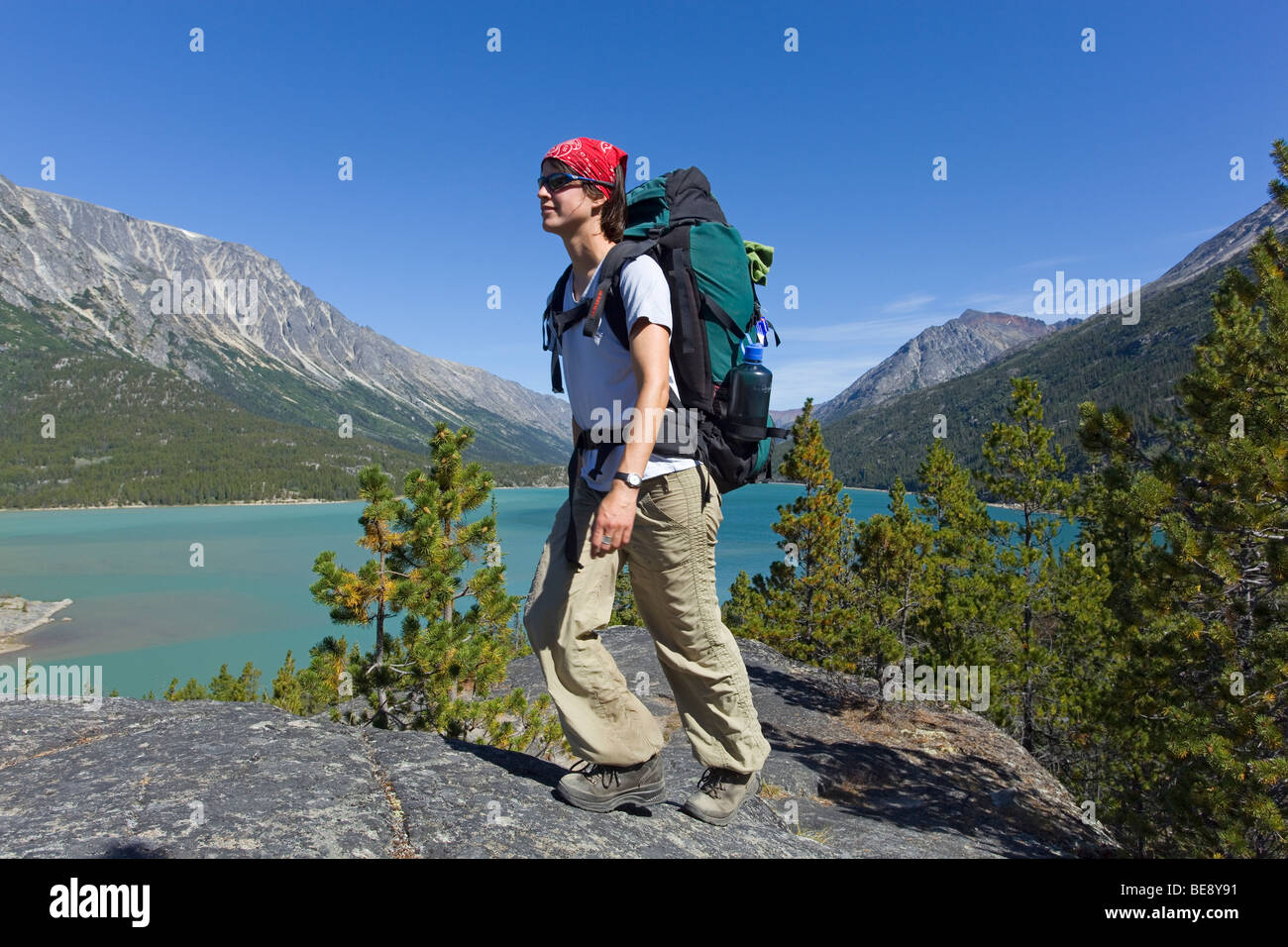 Young woman hiking, backpacking, hiker with backpack, historic Chilkoot Trail, Chilkoot Pass, Lake Bennett behind, - Stock Image