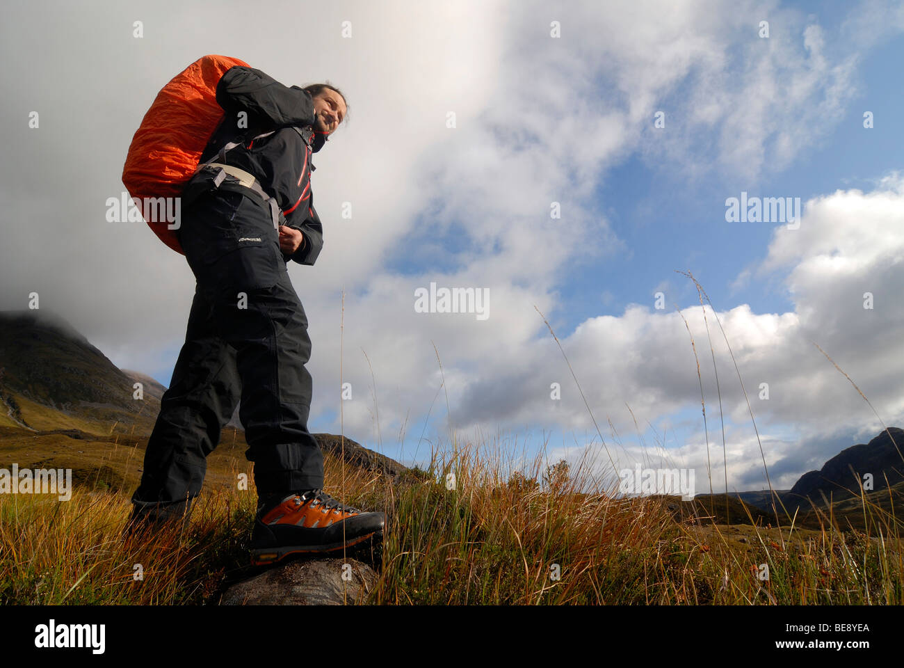Hiker with backpack on the road in the Scottish mountains in moody clouds in the sky, Scottish Highlands, Liathach, - Stock Image