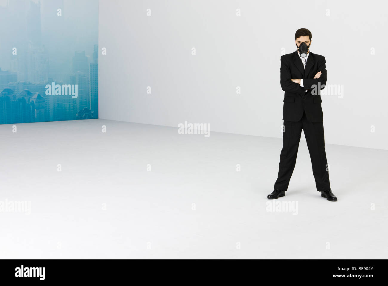 Businessman wearing gas mask, standing with arms folded, cityscape obscured by smog in background Stock Photo