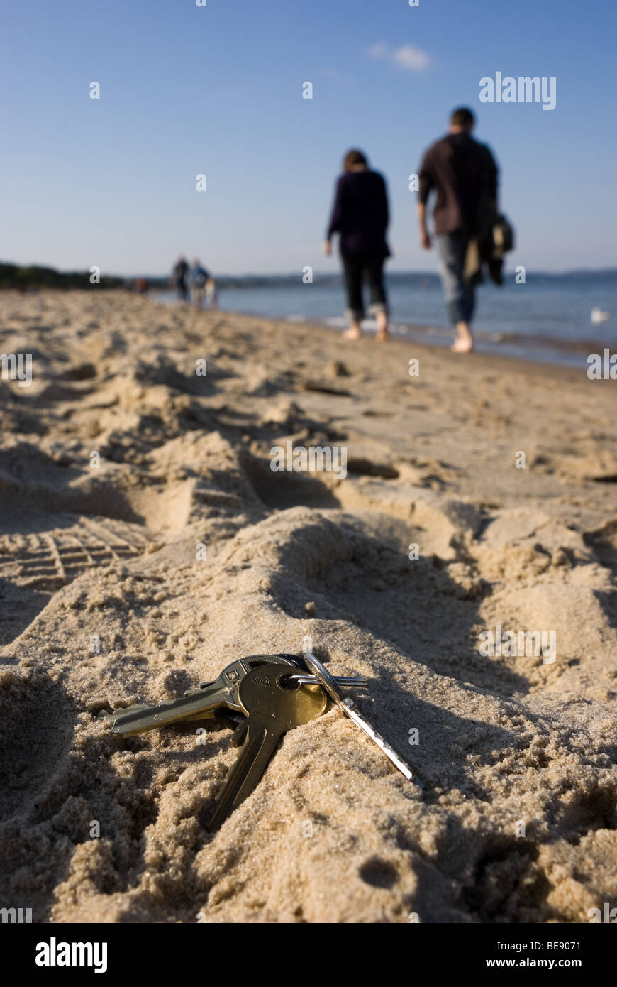 Bunch of keys lying on the sand (beach) - Stock Image