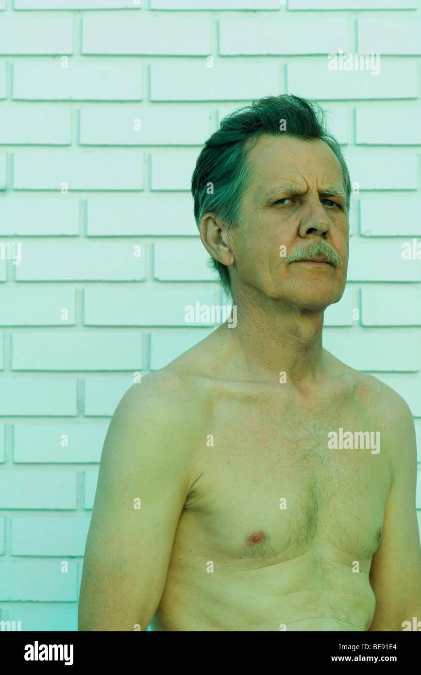 Bare-chested man furrowing brow, glaring at camera - Stock Image