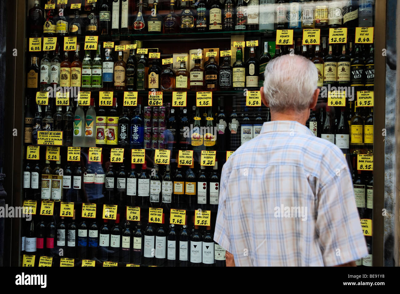 Person looking at alcohol prices in a traditional corner shop in Barri Gotic. Barcelona. Spain - Stock Image