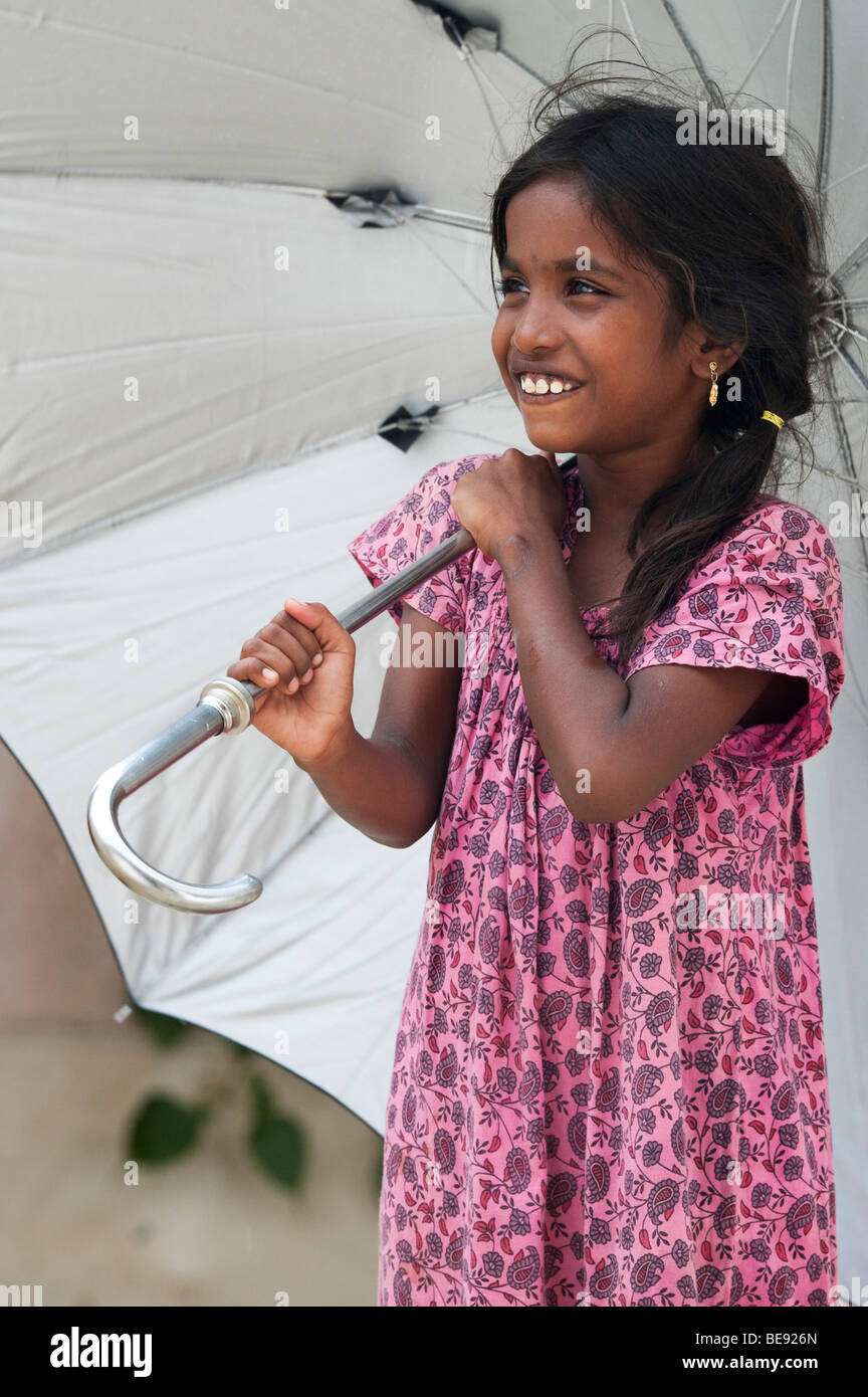 Young Indian girl under a large umbrella during the monsoon rain - Stock Image