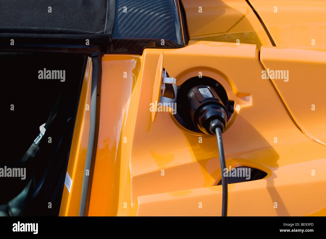 Electric car plugged into a socket, emission-free refueling, charging - Stock Image