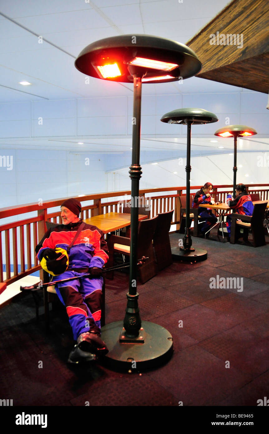 Skiers warming up under outdoor heaters, Ski Dubai indoor skiing hall in the Mall of the Emirates, Dubai, United - Stock Image