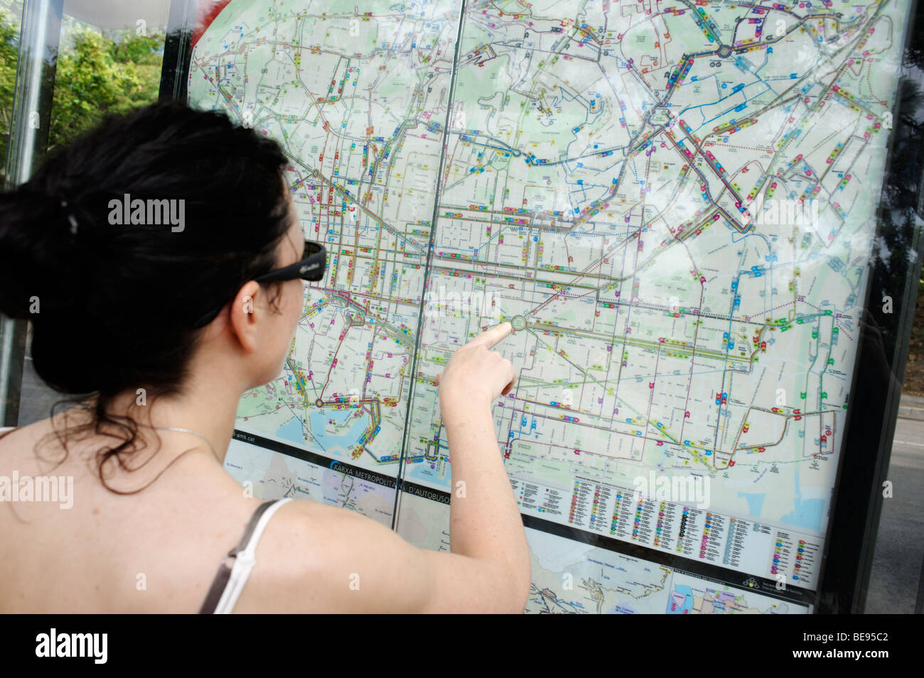 Woman studying a Barcelona city public transport map. Spain - Stock Image