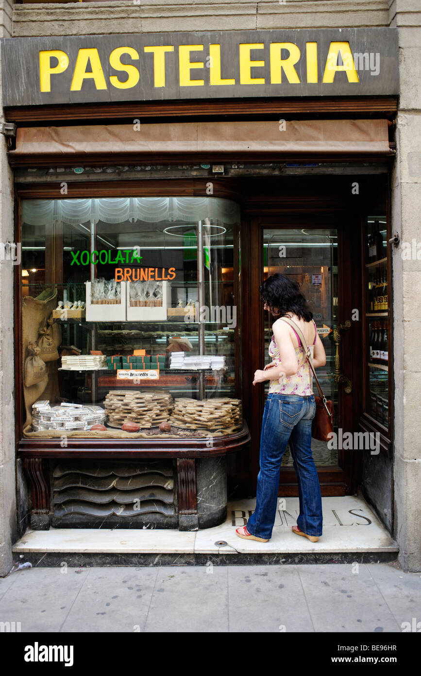 Girl window shopping in old traditional bakery . Barri Gotic. Barcelona. Spain - Stock Image