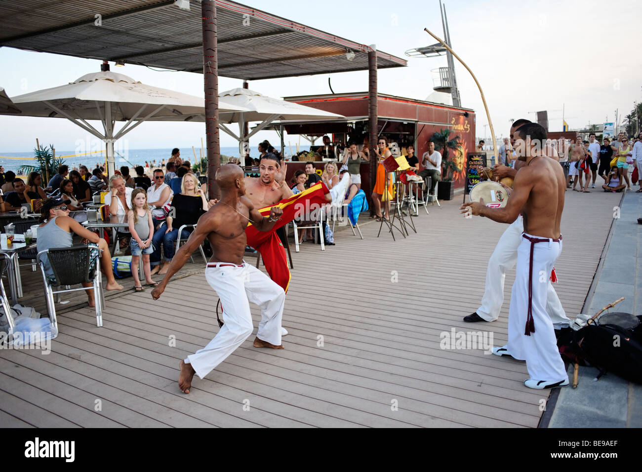 Afro-Brazilian Capoeira performers in front of city beach cafe at Barceloneta. Barcelona. Spain - Stock Image