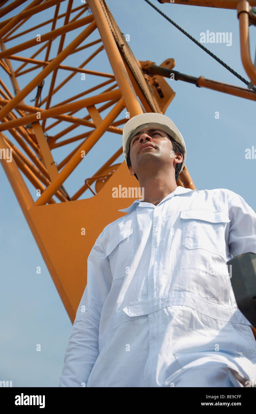 Man in work uniform looking into distance - Stock Image