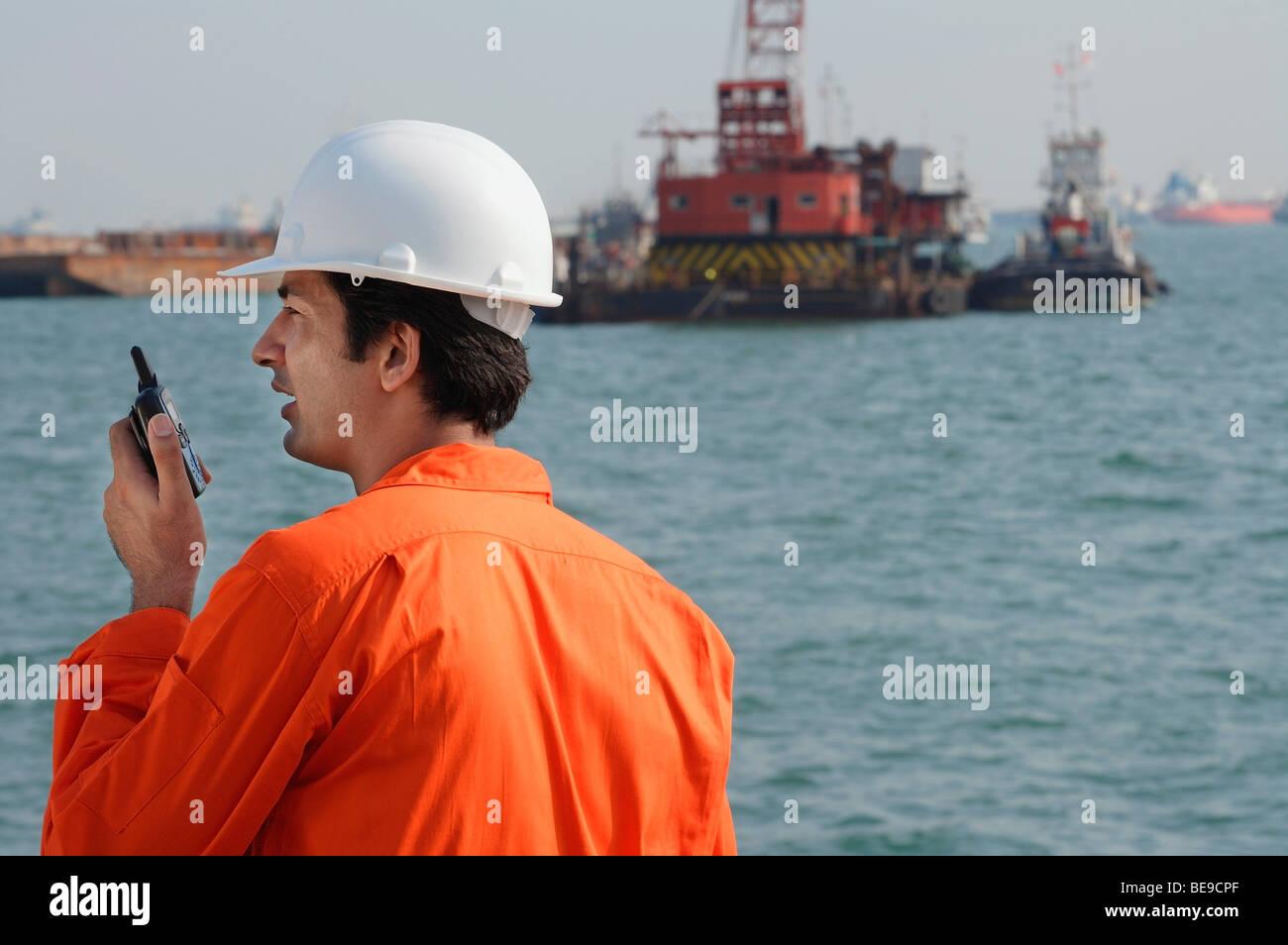 Man in work uniform talking into walkie talkie - Stock Image