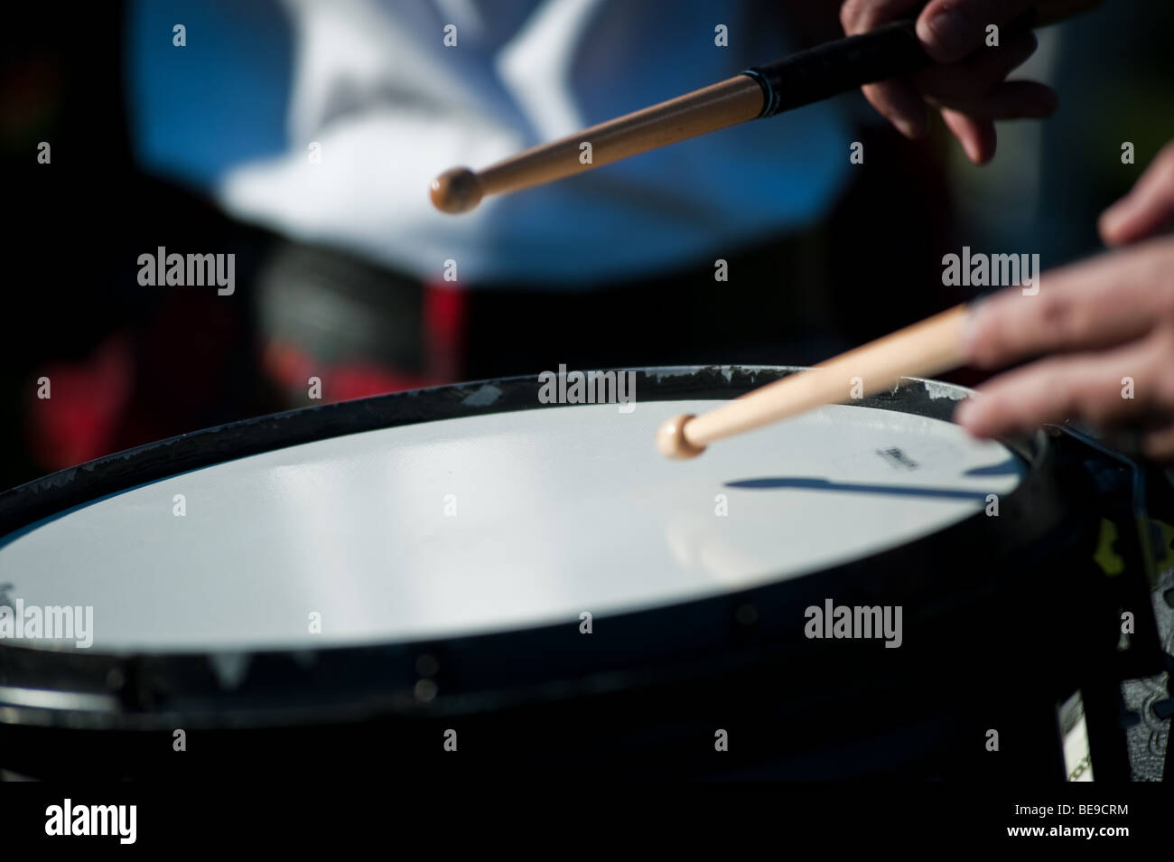 Pipe Band Snare Drummer playing with sticks while marching - Stock Image