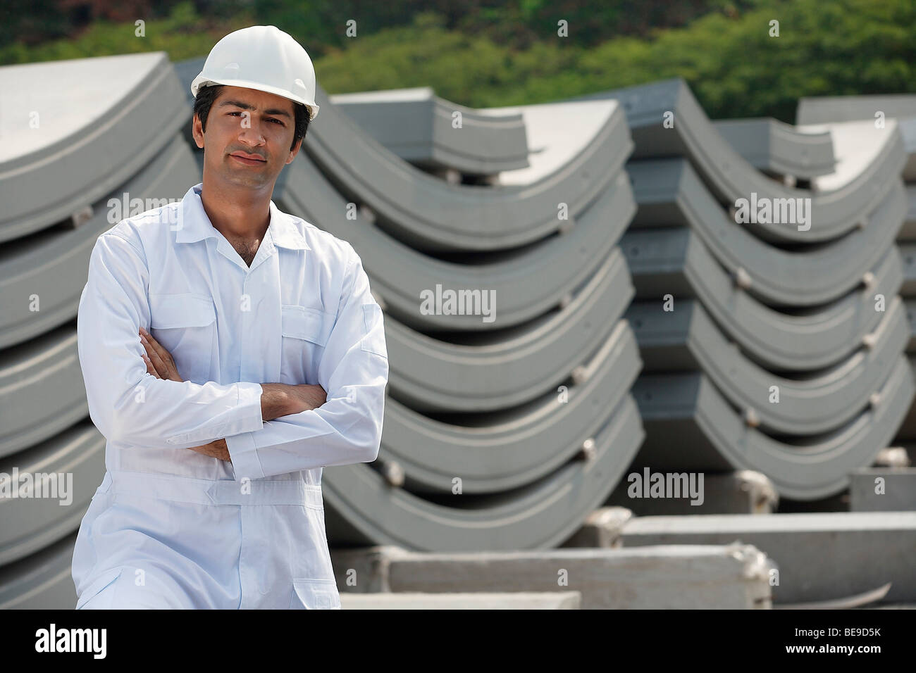 Man in work uniform arms crossed, looking at camera - Stock Image