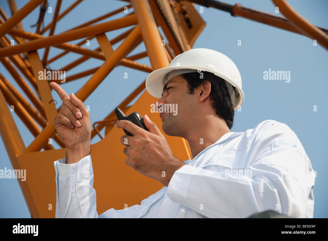 Man in work uniform pointing and using walkie talkie - Stock Image