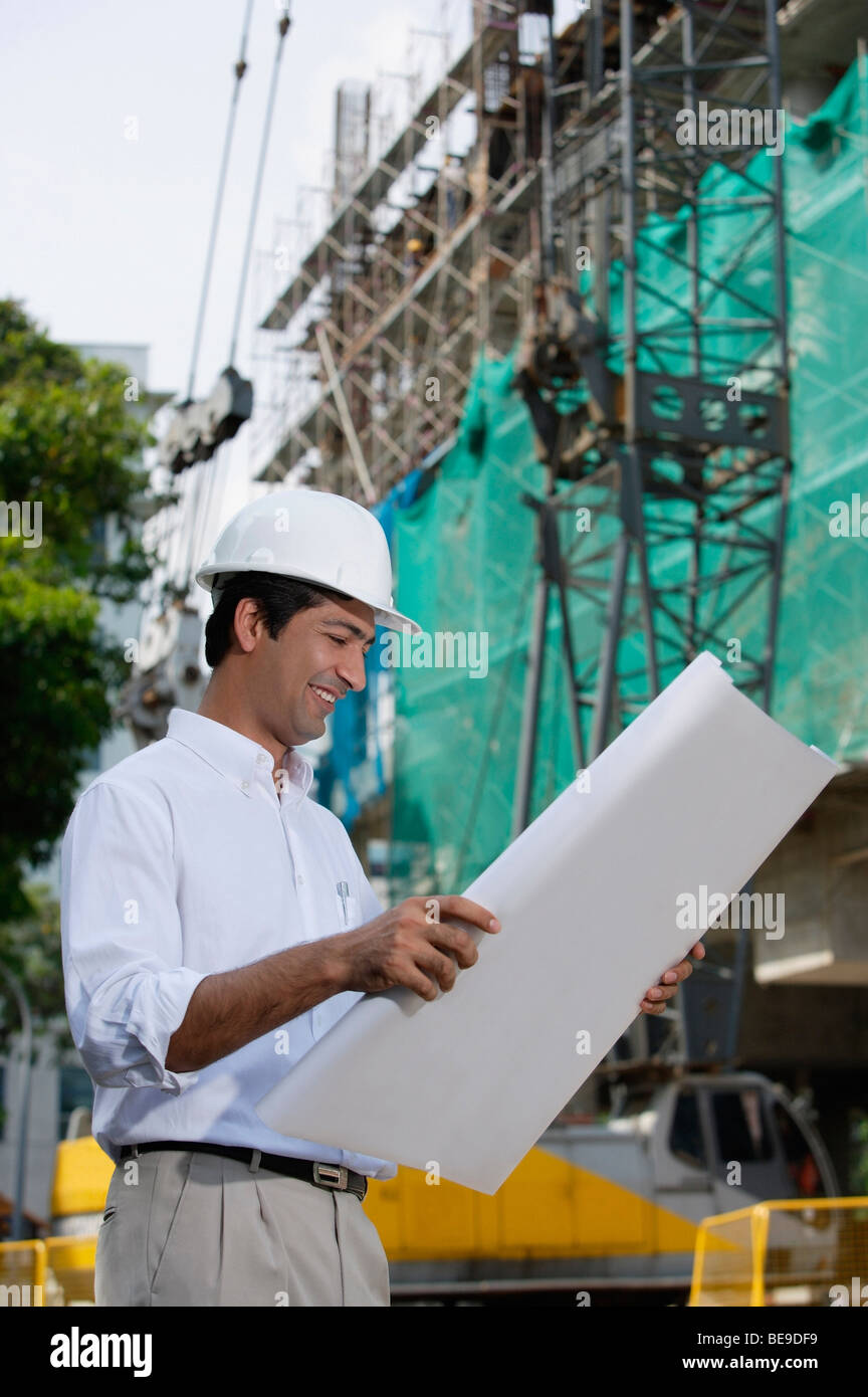 Man smiling while looking at plans - Stock Image
