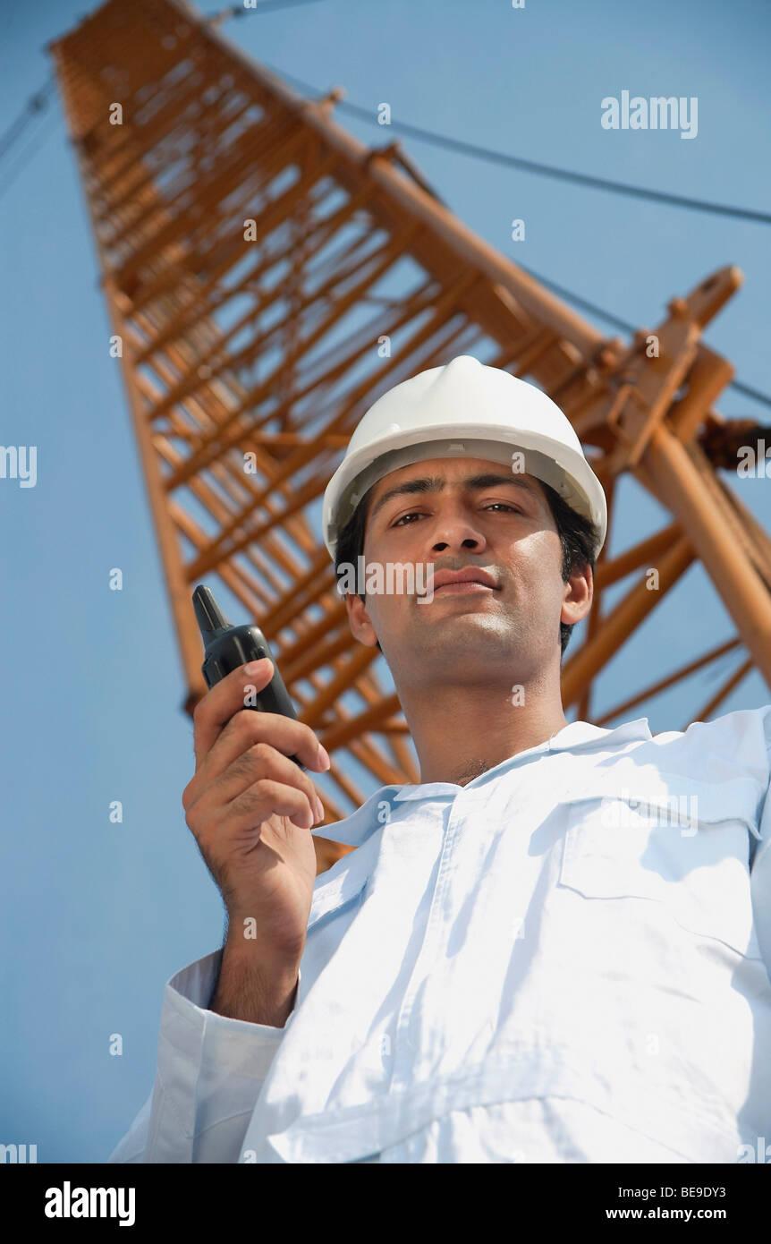 Man in work uniform looking down - Stock Image