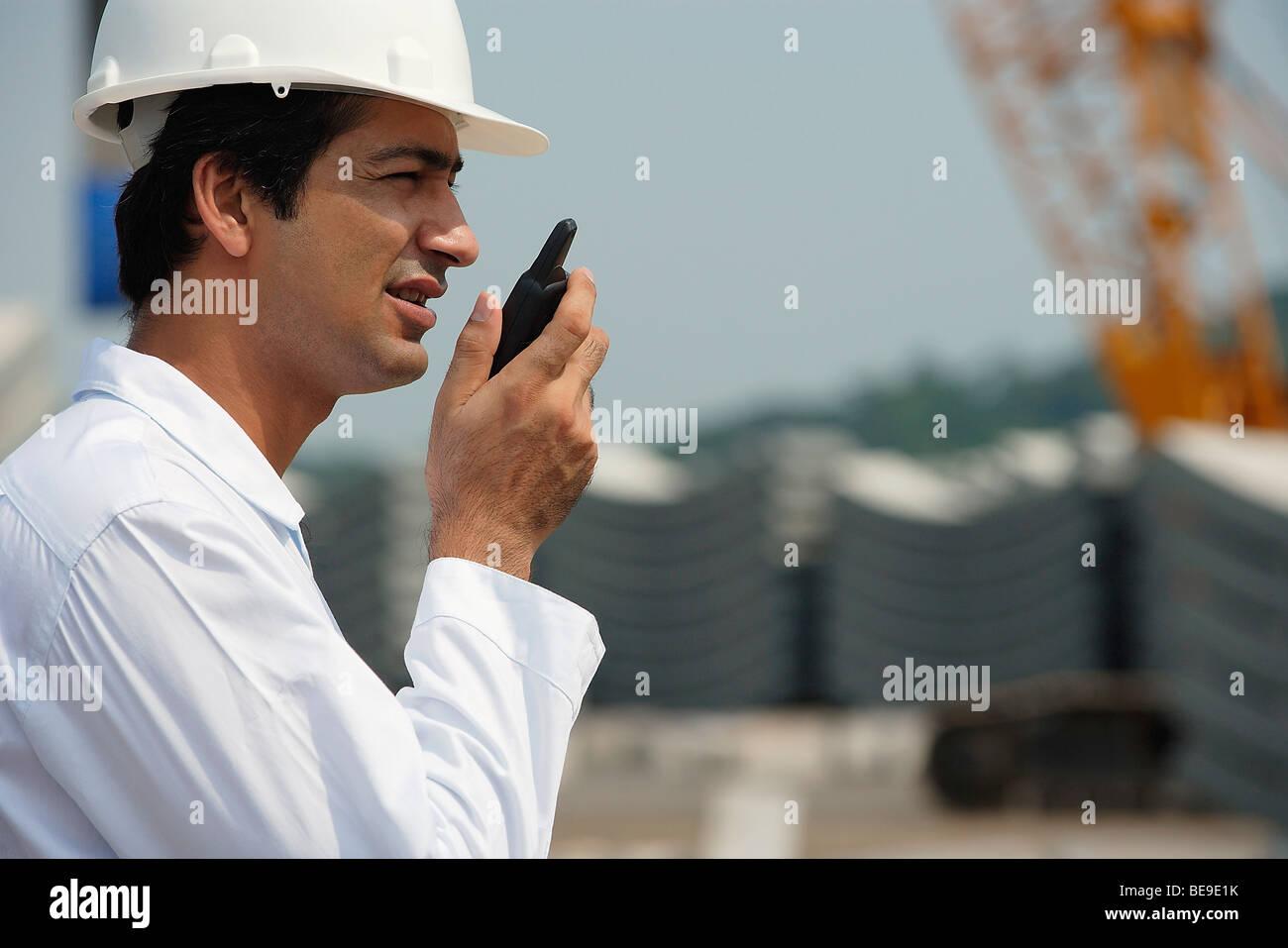 Man in work uniform, talking into walkie talkie - Stock Image