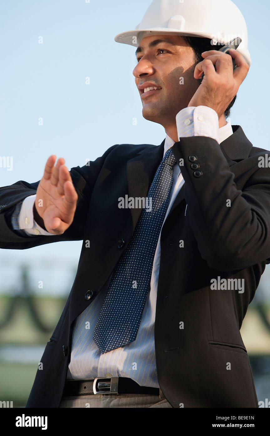 Man with helmet talking on mobile phone and gesturing - Stock Image