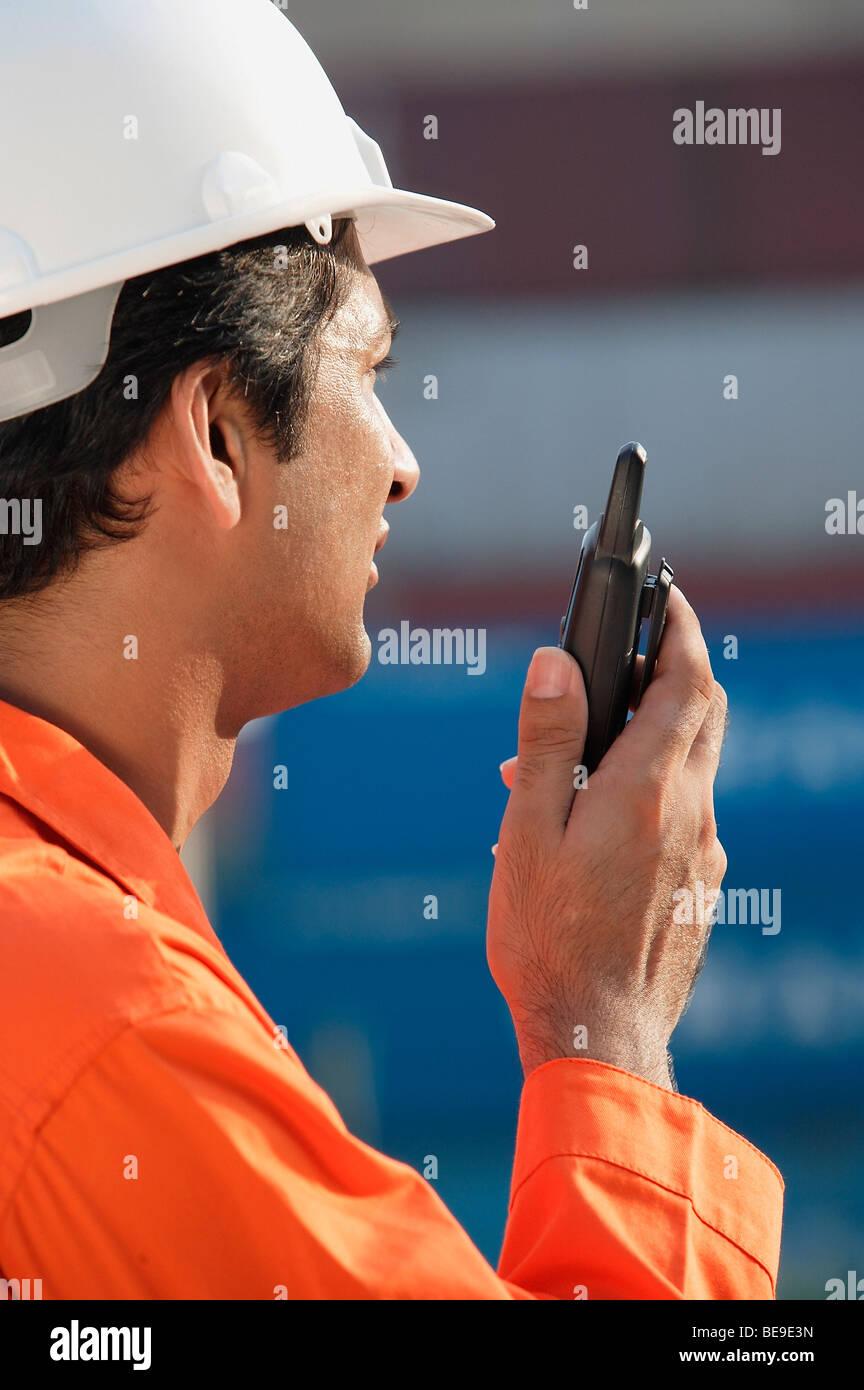 Man in work uniform using walkie talkie - Stock Image