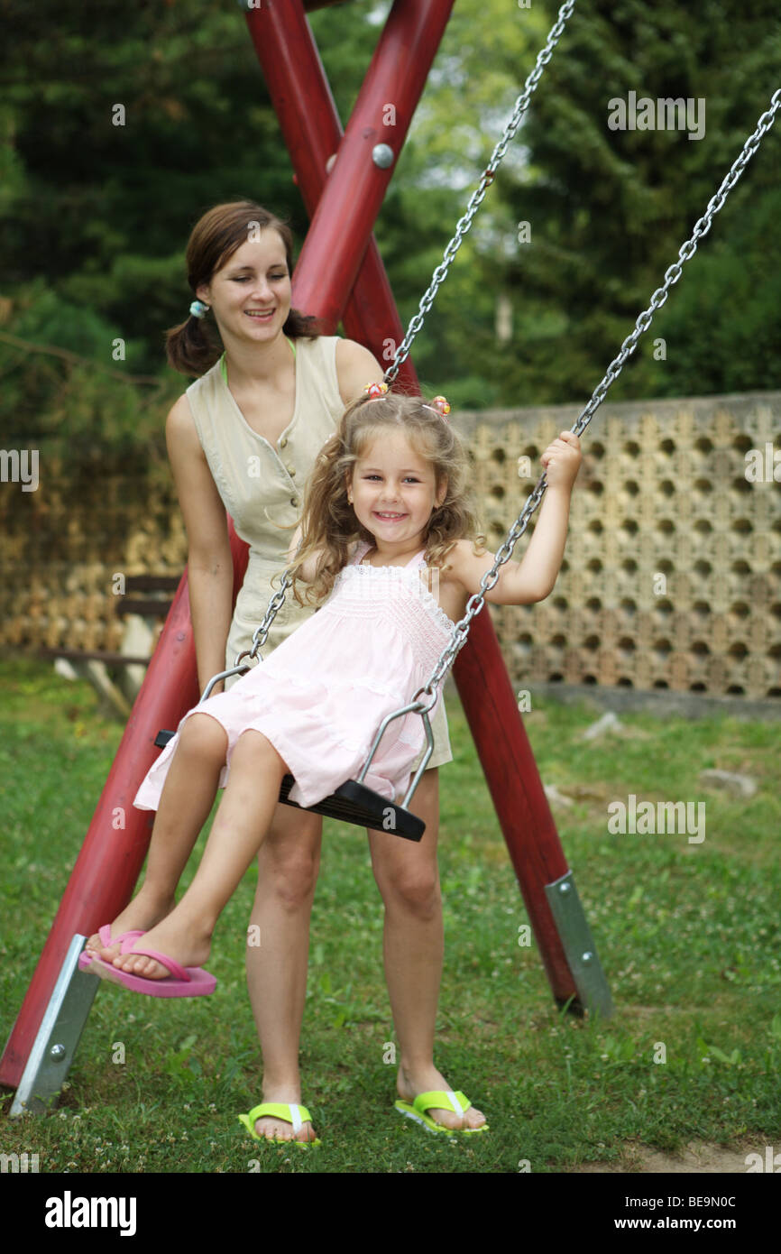 Mother and daughter playing in playground. Child is swinging on swing. Stock Photo