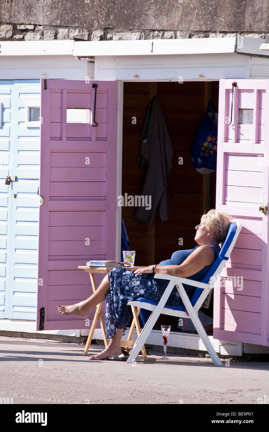 middle aged women sunbathing on deckchair by open doors of beach hut with book and glass of wine - Stock Image