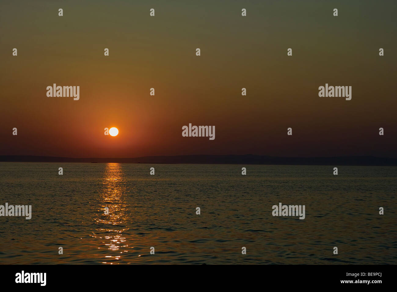 Beautiful sunset on island of Pag, Croatia, with a sun reflection on sea surface - Stock Image