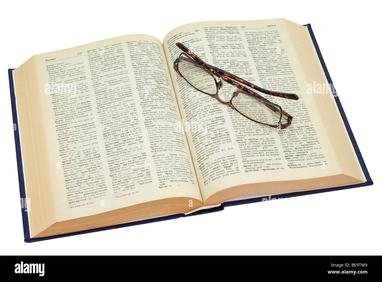 open yellowed old book with glasses, saved with clipping path - Stock Image