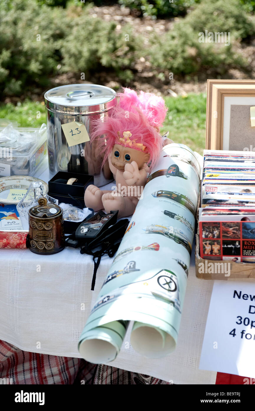 doll on a table with other items for sale - Stock Image
