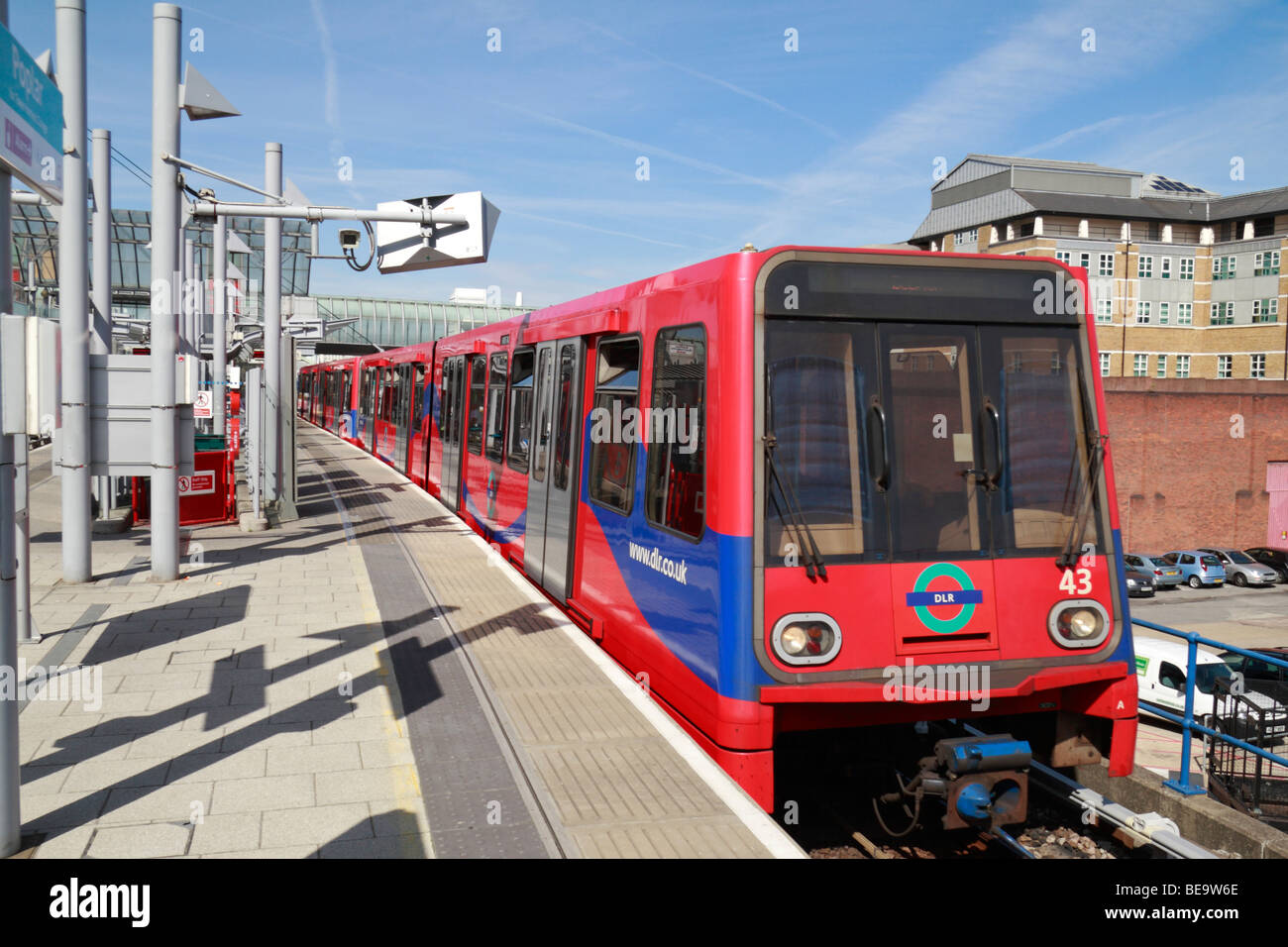 A Docklands Light Railway train pulling in to the platform at Poplar DLR Station, Isle of Dogs, London, UK. - Stock Image