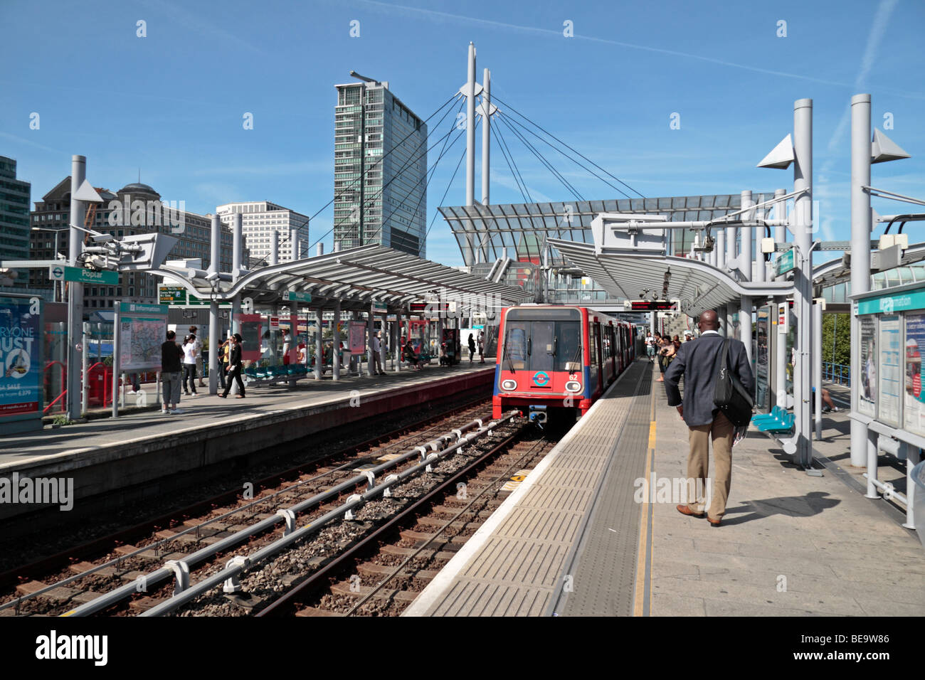 A Docklands Light Railway (DLR) train pulls into Poplar Station close to Canary Wharf, Isle of Dogs, London, UK. - Stock Image