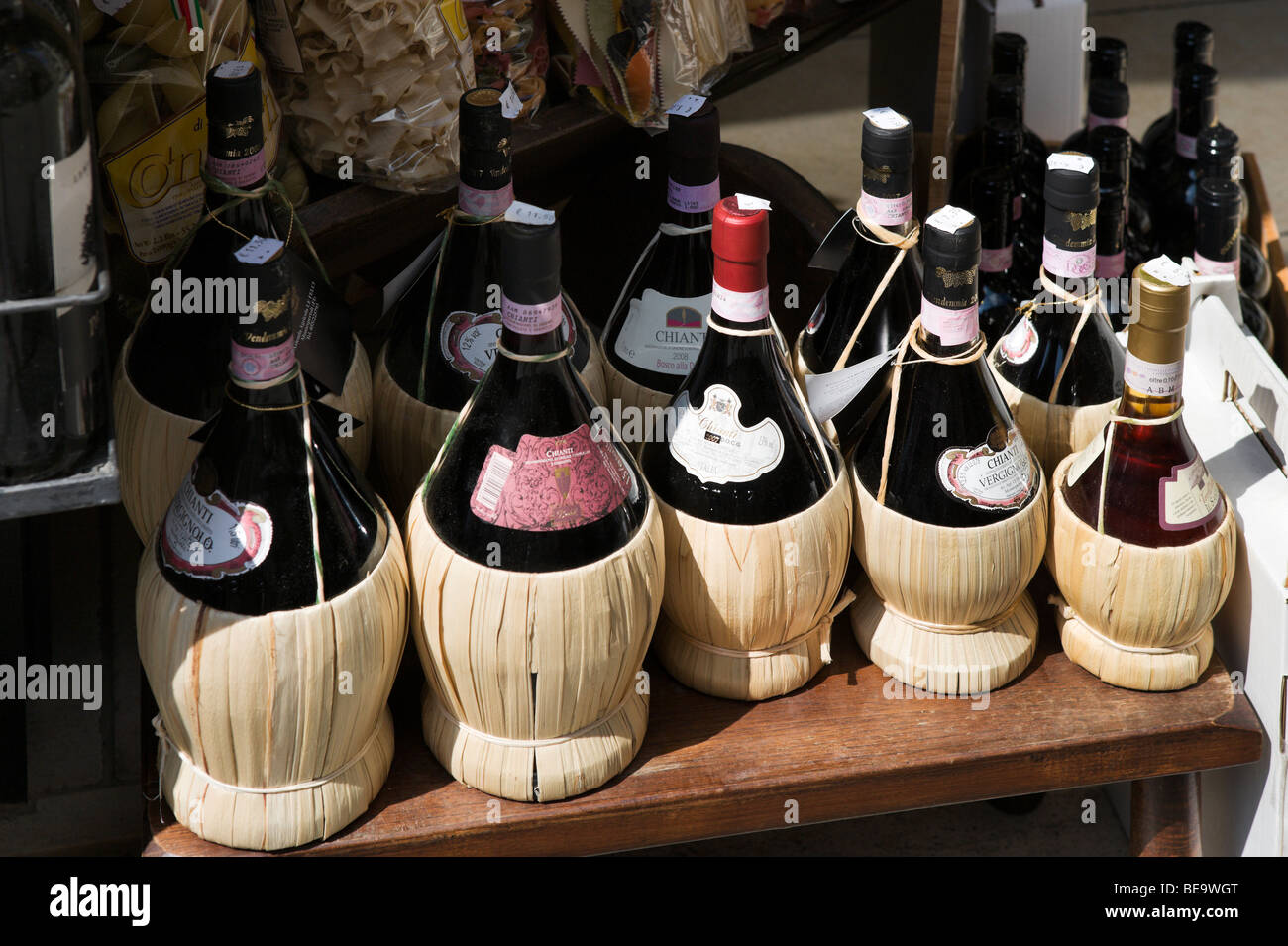 Shop selling local chianti wine in traditional bottles (fiaschi), the old town, San Gimignano, Tuscany, Italy - Stock Image