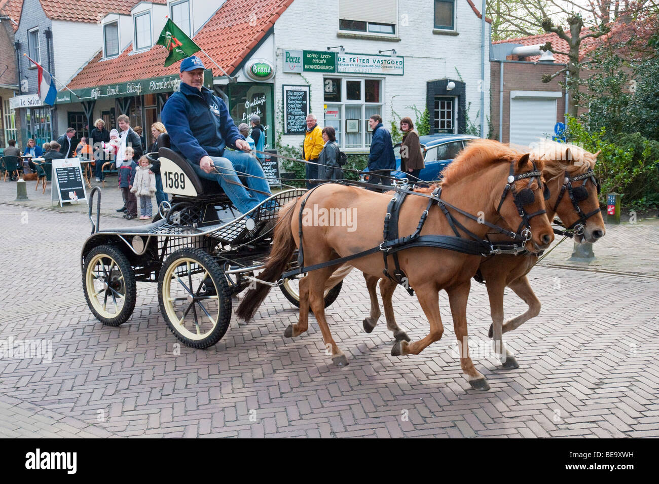 A horse carriage drives through the Dutch North Sea resort town of Burgh-Haamstede. - Stock Image