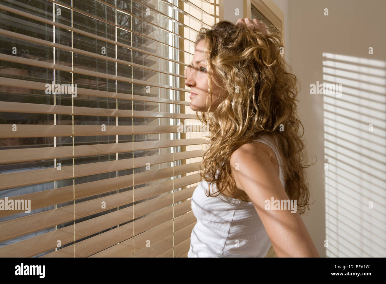 Curious woman in bedroom peering through blinds in morning - Stock Image