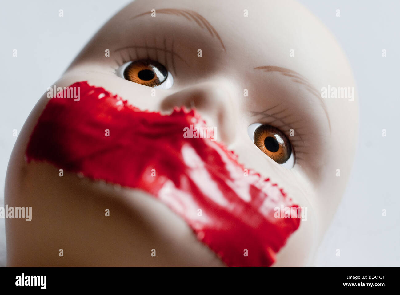 Close up of face of girl doll with red tape on mouth Stock Photo