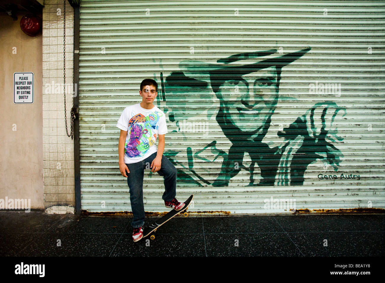 A skateboarder poses near a mural of Gene Autry, Hollywood Boulevard, Los Angeles, California, United States of - Stock Image