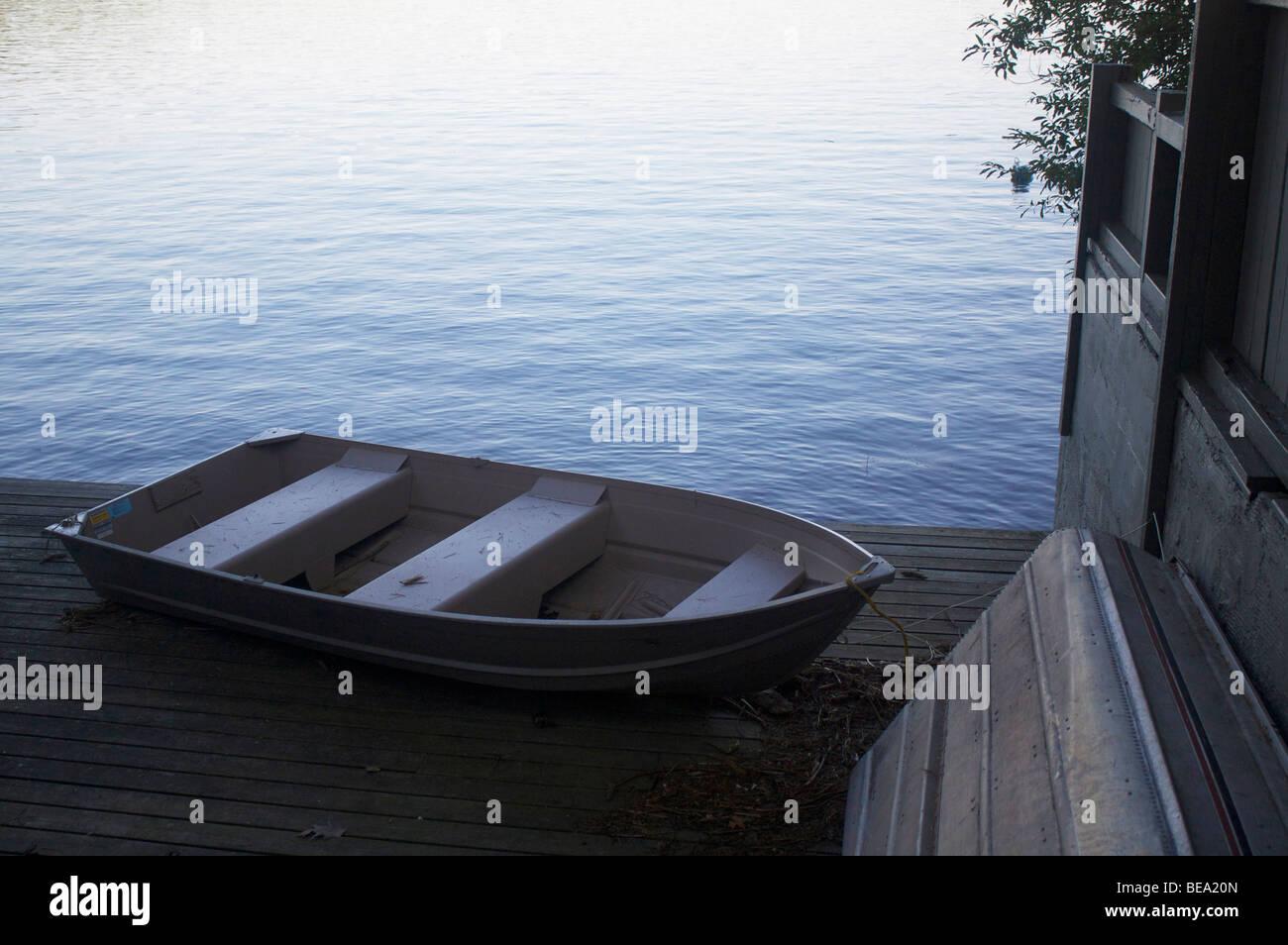 Row boats docked by a lake - Stock Image