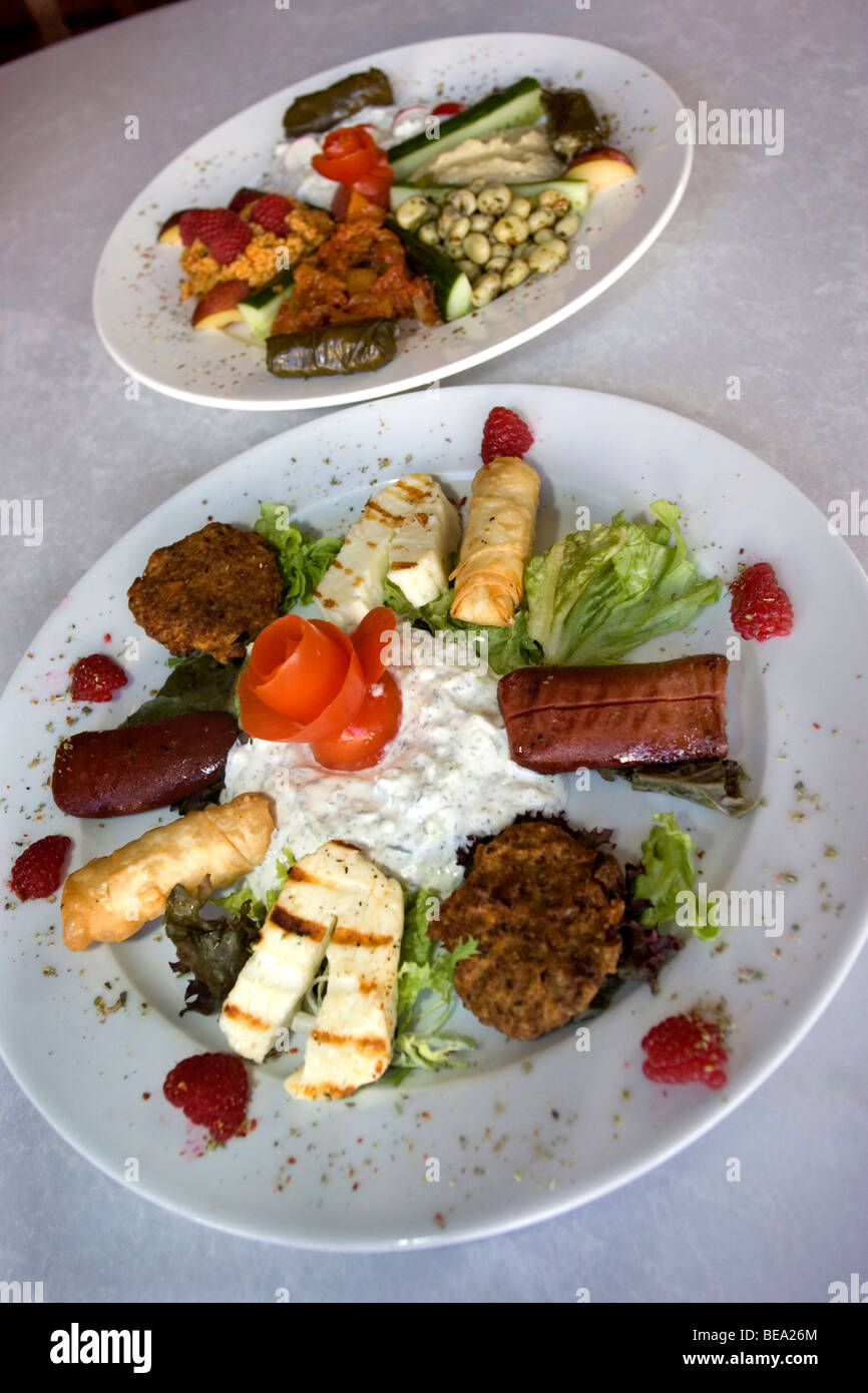 Close-up of a plate of Hot Greek mezze platter (FRONT) and a plate of cold mezze (BEHIND) in a modern Greek restaurant - Stock Image