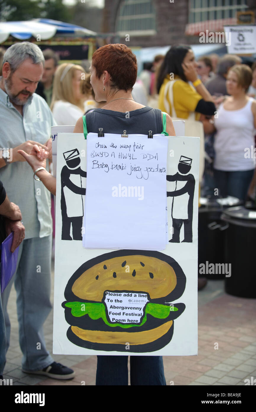 Woman in a sandwich board getting people to contribute a line to a poem at the Abergavenny food festival, Monmouthshire - Stock Image