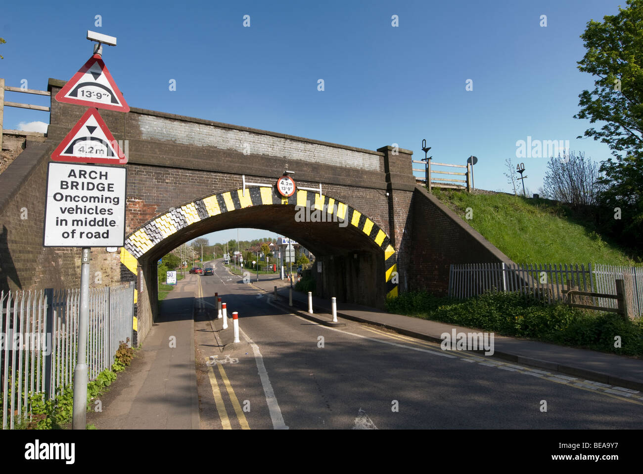Road markings guiding traffic single file beneath a height restricted railway bridge in England - Stock Image