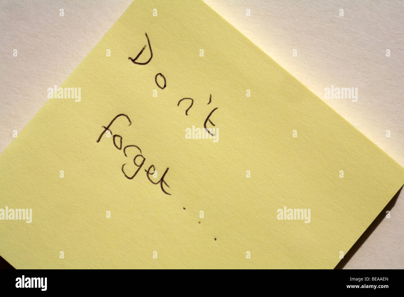 Don't forget reminder message written on yellow post-it note close up set on white background - Stock Image