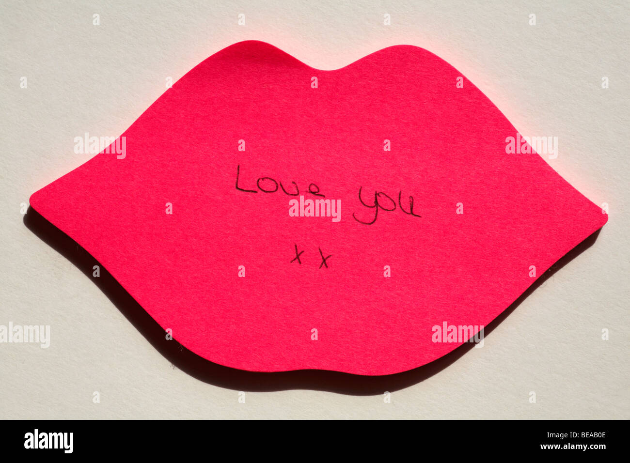 Love you xx message hand written on pink lips post it note close up isolated on white background - Stock Image