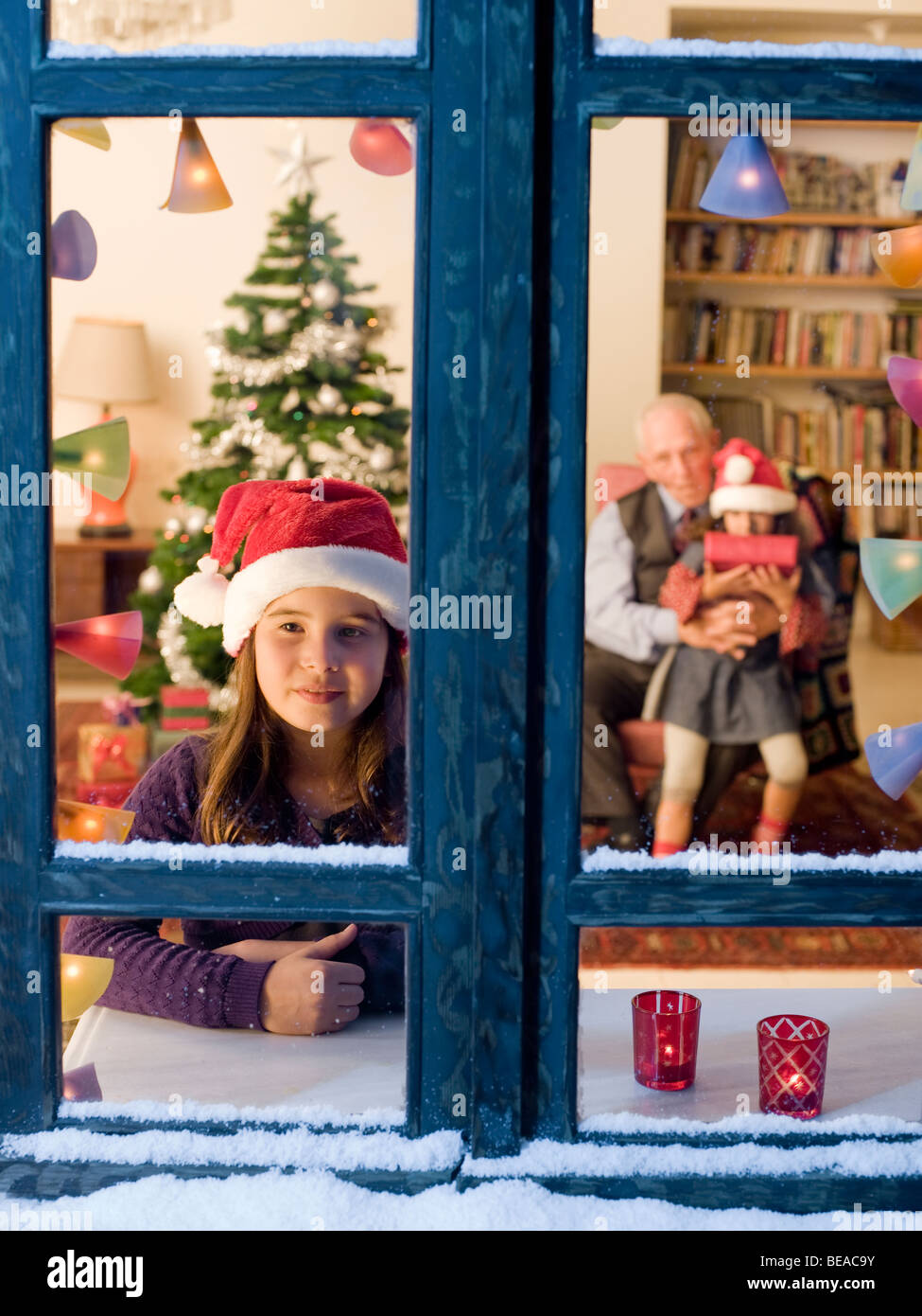 Child looking outside on Christmas eve. - Stock Image
